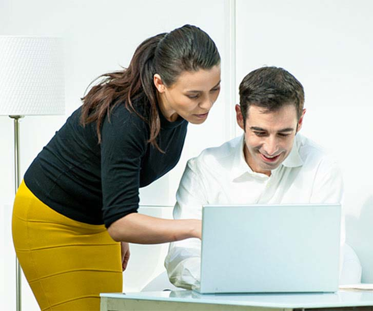 Male and female looking at laptop